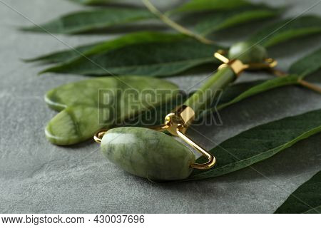 Face Roller, Gua Sha And Twig On Gray Textured Background
