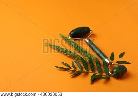Green Face Roller And Leaves On Orange Background