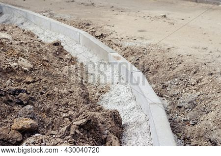 Installation Of New Curbs. The Gray Curbs Are Fixed In Cement Mortar. Construction Of A New Road Or