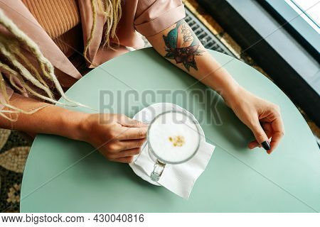 Caucasian Woman With Dreadlocks Sitting In Cafe.