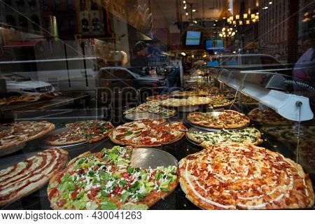 2018 May 7. Pizza resting on a pizza counter behind window with reflection of New York city
