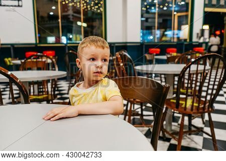 Child Sitting In Cafe And Waiting Pizza.