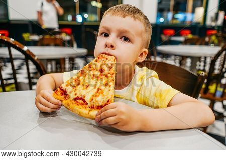 Child Eats Pizza In Cafe, Close Up.