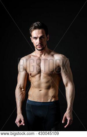 Portrait Of An Attractive Muscular Man On A Dark Background