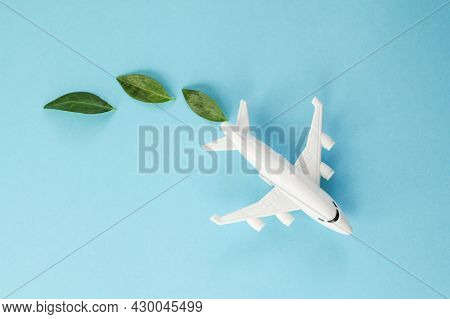 Sustainable Aviation Fuel. White Airplane Model, Fresh Green Leaves On Blue Background. Clean And Gr