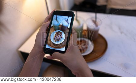 Top View. Woman Taking A Photo Of The Mini Sweets Cake And Coffee With A Mobile Smartphone. Photogra