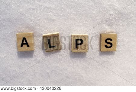 Alps Word On A White Clean Snow. Alps Mountains Is Written On A Snow With Wooden Letters.