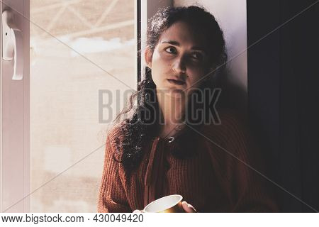 Cold Autumn Days - A Young Multi-racial Female Drinks Coffee In A Cozy Windowsill. Middle-eastern Or