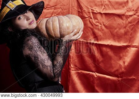 Halloween Lady Wearing Witch Cup And Holding A Big Halloween Pumpkin. A Woman In Witch Hat And Hallo
