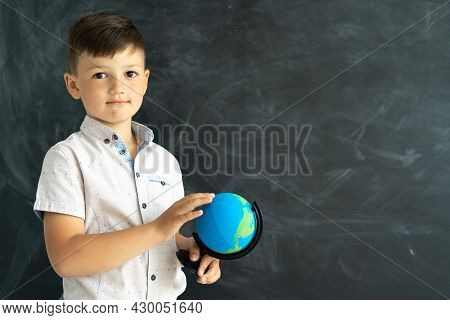 Caucasian Schoolboy At A Geography Lesson Stands Near The Blackboard In The Classroom. Schoolboy Or