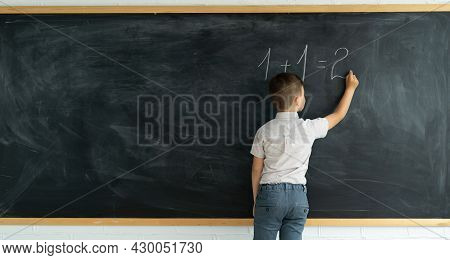 Back View Of A Child Writes With Chalk On A Blackboard Solution Of An Example In Mathematics. Elemen