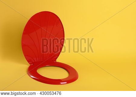 New Red Plastic Toilet Seat On Yellow Background, Space For Text