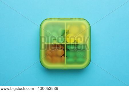 Pill Box With Medicaments On Light Blue Background, Top View
