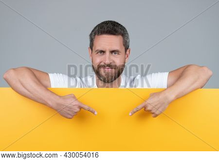 Heerful Mature Bearded Man Behind Yellow Paper Point Fingers On Copy Scape, Suggestion