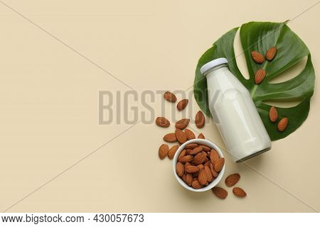 Bottle Of Vegan Milk And Almond Nuts On Beige Background, Flat Lay. Space For Text
