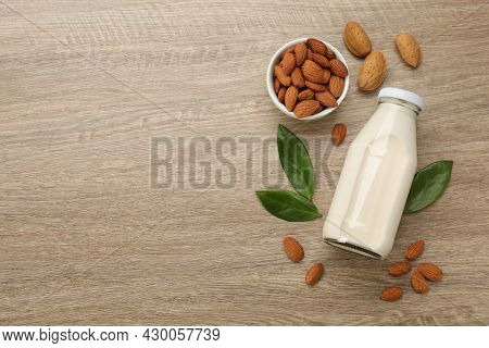 Delicious Almond Milk And Nuts On Wooden Table, Flat Lay. Space For Text