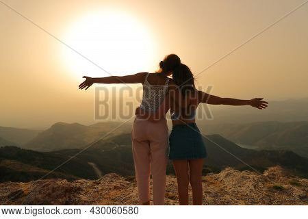 Two Happy Friends Celebrating Outstretching Arms At Sunset In The Mountain