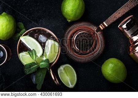 Preparation Moscow Mule Cocktail With Ginger Beer, Vodka, Lime And Ice. Copper Bar Tools. Black Bar