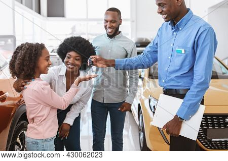 Positive Auto Salesman Giving Car Key To Cute Black Girl And Her Parents At Dealership Store