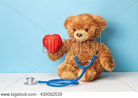Childrens Doctor Or Family Doctor. Teddy Bear With A Stethoscope Is Holding Red Heart