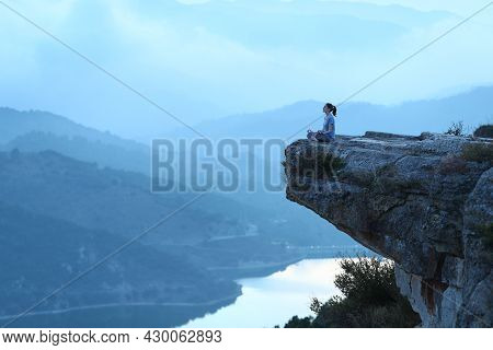 Full Body Portrait Of A Woman Doing Yoga Exercise In The Top Of A Cliff On Blue Ambient