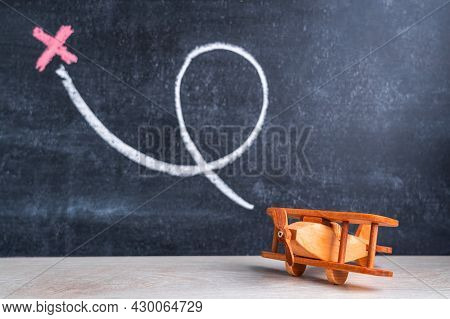 A Wooden Biplane Toy On The Background Of A Blackboard With A Loop And A Cross Drawn In Chalk. The C