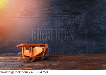 Wooden Toy Airplane On The Background Of A Chalk Board. Small Biplane Made Of Wood On A Dark Backgro
