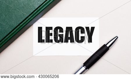 On A Light Gray Background Lies A Pen, A Green Notebook And A White Card With The Text Legacy. Busin