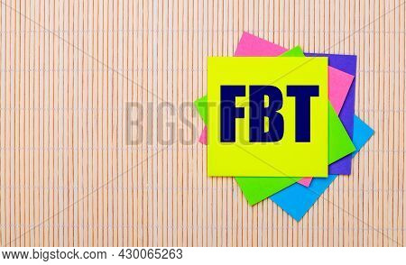 On A Light Wooden Background, Bright Multicolored Stickers With The Text Fbt Fringe Benefit Tax
