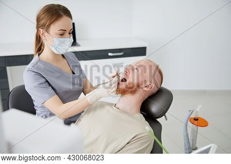 Portrait Of Young Female Dentist Standing By Mid Adult Man In Clinic. Female Dentist Repairing Patie