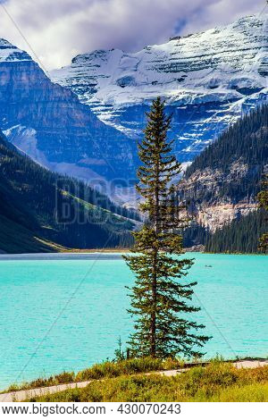 Beautiful day. Glacial Lake Louise in Banff Park, Canadian Rockies. The lake with azure water is surrounded by mountains and forests. The concept of ecological, active and photo tourism