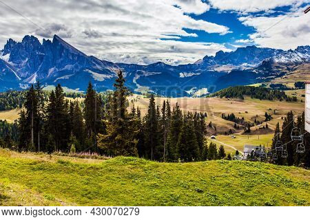 The Dolomites, Italy. Magnificent rocky ridge borders a hilly valley Alpe di Siusi. Picturesque grassy hills. Sunny day for photographing and hiking.  concept of walking, ecological and photo tourism