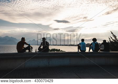 Antalya,turkey-july,2021: Group Of Young Traveler People Sitting On Stone Parapet And Looking At To