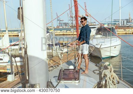 Pleased young man prepare rope for sailing on yacht in sea or ocean. Guy wear shorts, shirt and glasses. Marina or harbor. Concept of vacation or tourism on sea. Summertime. Sunny daytime