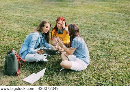 Teenage Girls Are Sitting On A Green Lawn In A Park With A Backpack And A Digital Tablet And Are Pre