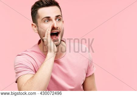 Young Handsome Man Shouting And Screaming Loud To Side With Hand On Mouth And Copy Space For Text On