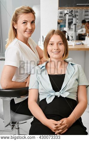 Cheerful Young Woman Having Appointment With Stomatologist. Female Dentist In White Work Shirt Sitti