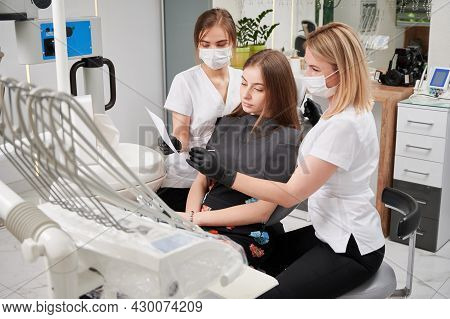 Beautiful Young Woman Sitting In Dental Chair While Stomatologists In Medical Masks Analyzing Dental