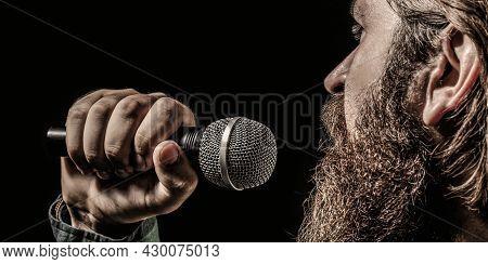 Bearded Man In Karaoke Sings A Song Into A Microphone. Male Attends Karaoke. Male Singing With A Mic