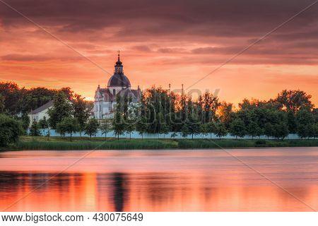 Nesvizh, Minsk Region, Belarus. Corpus Christi Church And Castle Pond Lake At Summer Sunset Evening