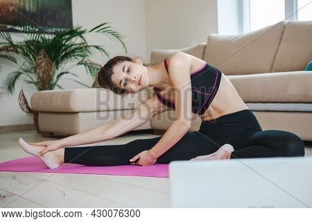 Sporty Woman On Floor Stretching In Beautiful Style. Sport, Healthy Lifestyle. Healthy Young Female