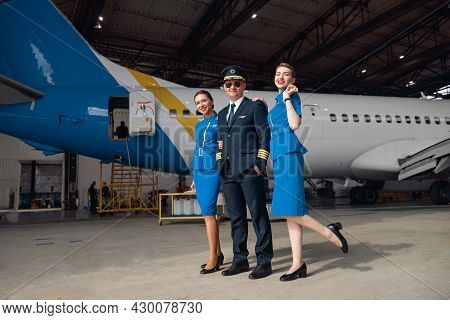 Full Length Shot Of Pilot In Uniform And Aviator Sunglasses Standing Together With Two Air Stewardes