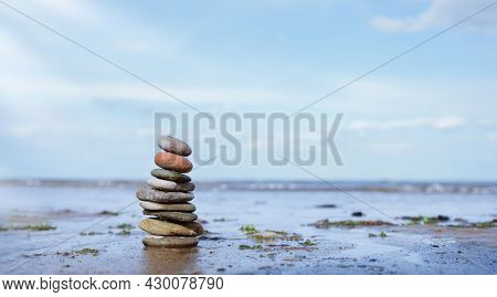Pebble Tower By Seaside With Blurry Seascape, Stack Of Zen Rock Stones On The Sand, Stones Pyramid O