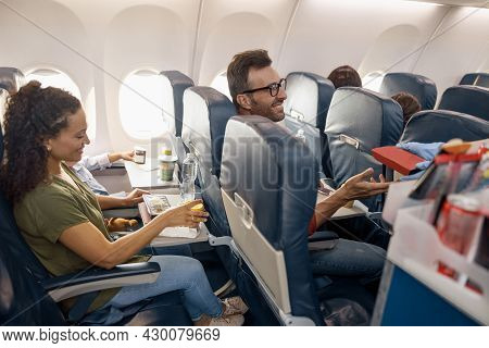 Cheerful Passengers Smiling, Waiting For Female Flight Attendant Serving Lunch On Board