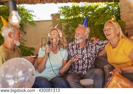 Group Of Cheerful Senior People Having A Birthday Party For A Friend, Having Fun Singing Karaoke