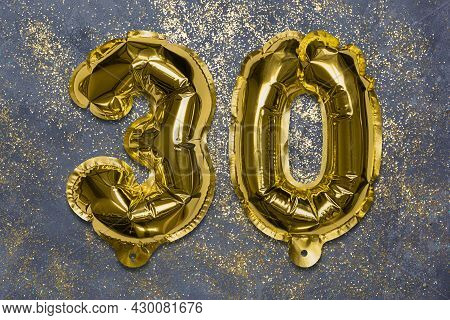 The Number Of The Balloon Made Of Golden Foil, The Number Thirty On A Gray Background With Sequins.