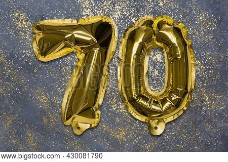 The Number Of The Balloon Made Of Golden Foil, The Number Seventy On A Gray Background With Sequins.