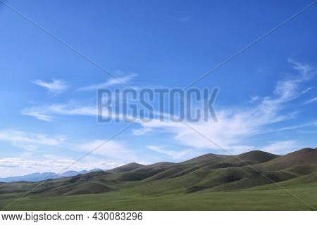 The green slope of the mountain under blue sky and white clouds