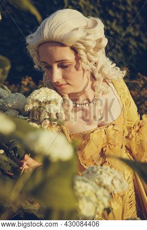 Portrait Of Blonde Woman Dressed In Historical Baroque Clothes With Old Fashion Hairstyle, Outdoors