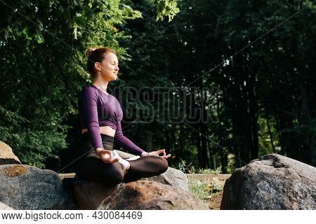 Meditation, Yoga, Spirituality And Mindfulness Concept. Young Woman In Sportswear Practicing Meditat
